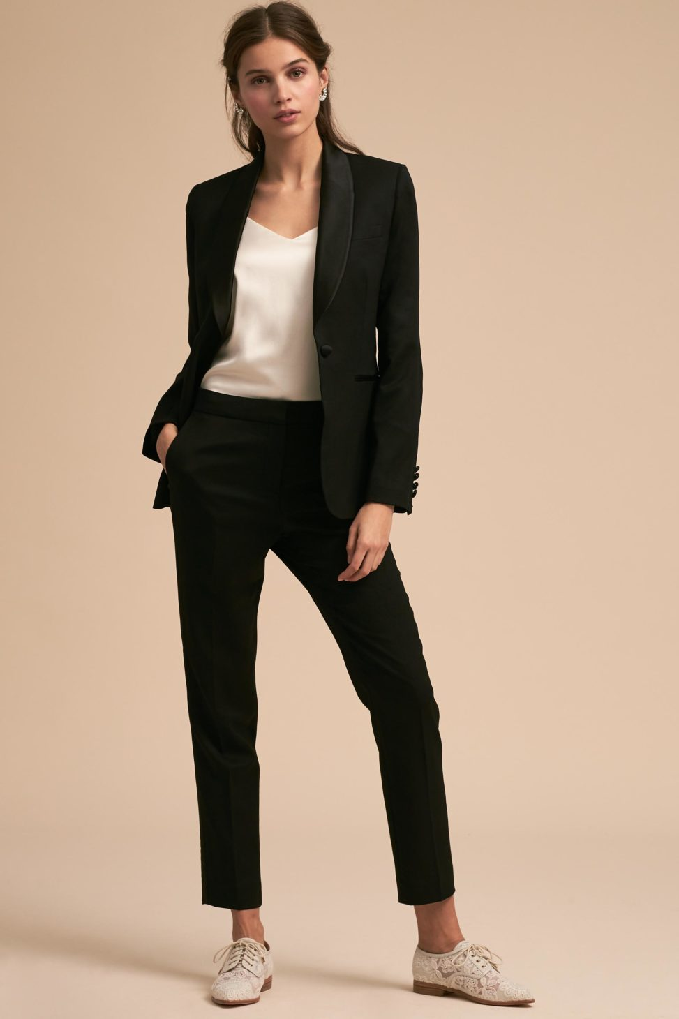 A woman stands, dressed in a black tuxedo jacket and black pants with white shoes.