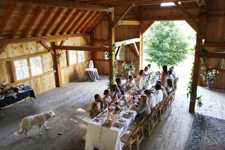 People eating at long family table set with white linen inside rustic barn, with a white dog