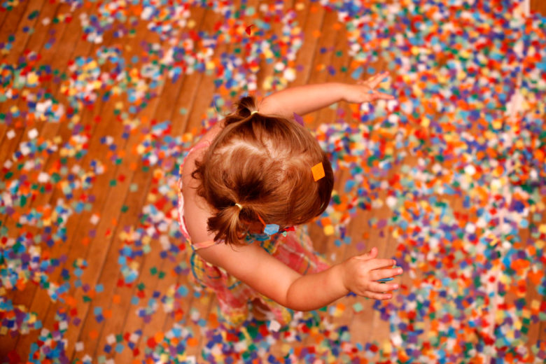 Overhead view of small girl with pigtails playing in confetti