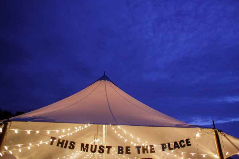 """Party tent illuminated with white string lights with a banner that reads """"This must be the place"""""""
