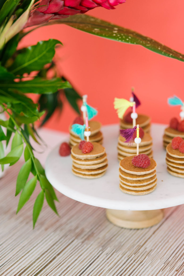 mini pancake stacks with raspberries and toothpicks with tassels on white pedestal platter