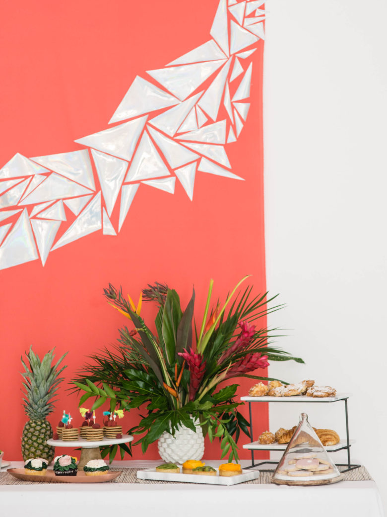 brunch party spread in front of coral backdrop with holographic triangles, with tropical plants and a pineapple