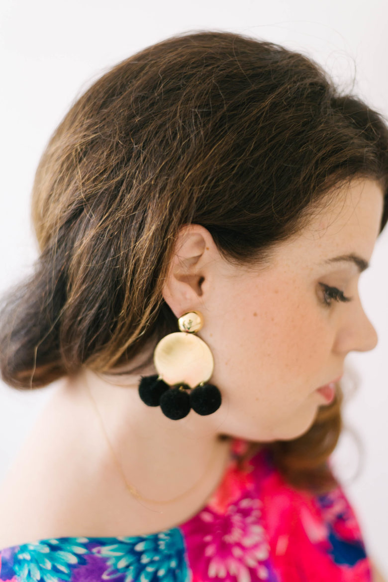 side portrait of woman wearing circular gold earrings with black poms