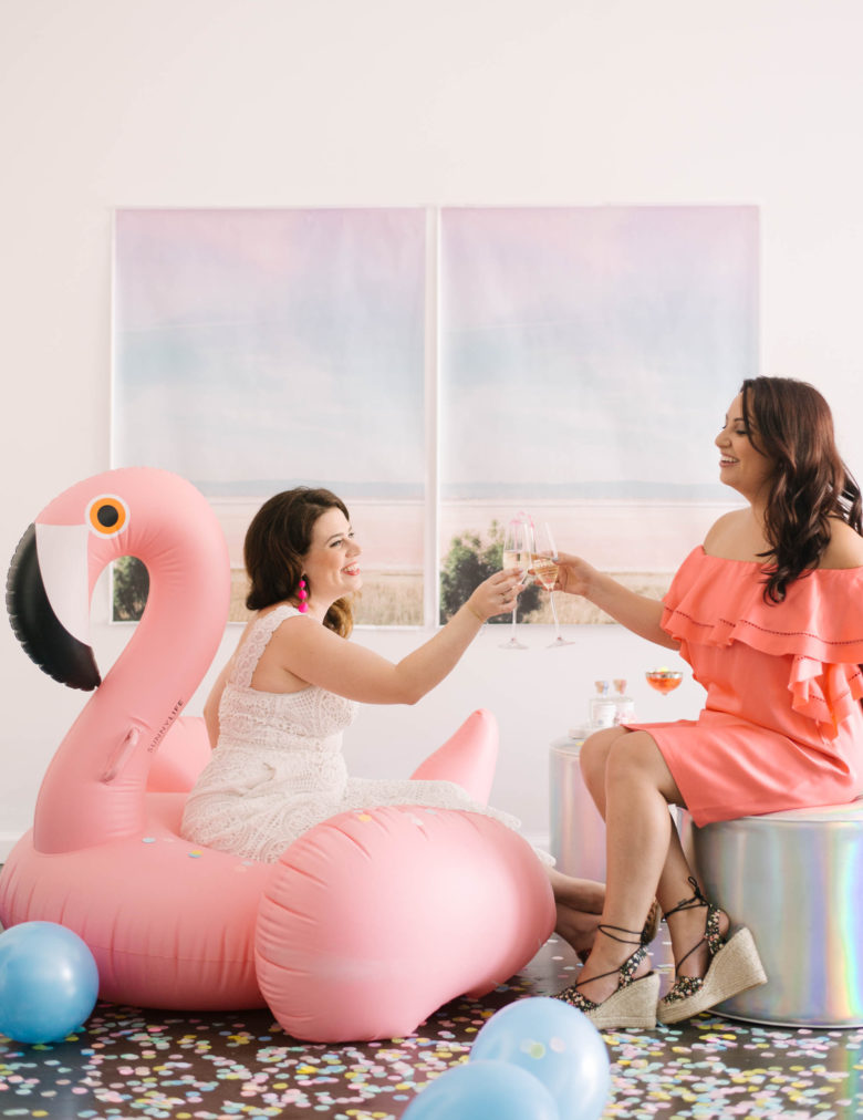 Two women toasting champagne, one on an inflatable pink flamingo, the other on a holographic pouf