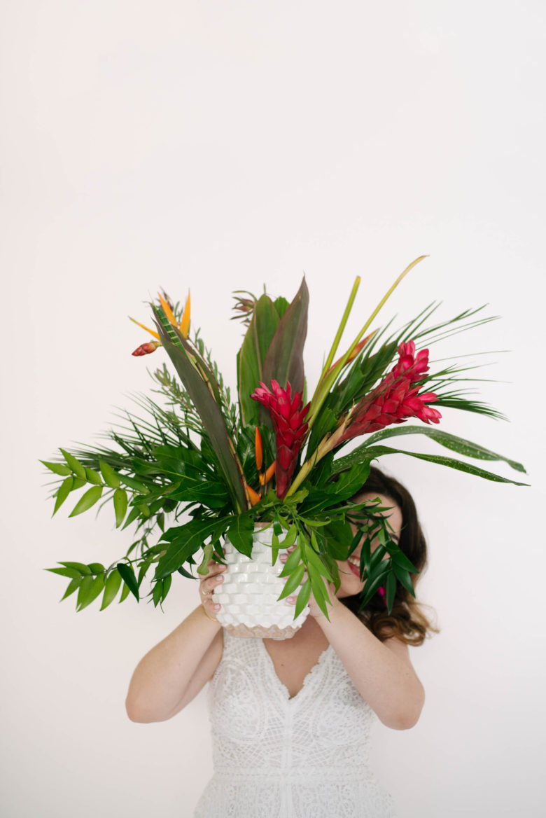 woman in white jumpsuit holding pineapple vase with tropical foliage