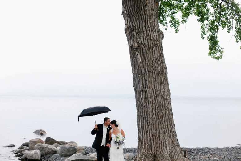 Newly wed couple under giant tree in front of water with large rocks, with groom holding black umbrella overhead