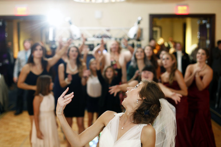 Bride throwing bouquet over shoulder to a group of women and girls in formal wear