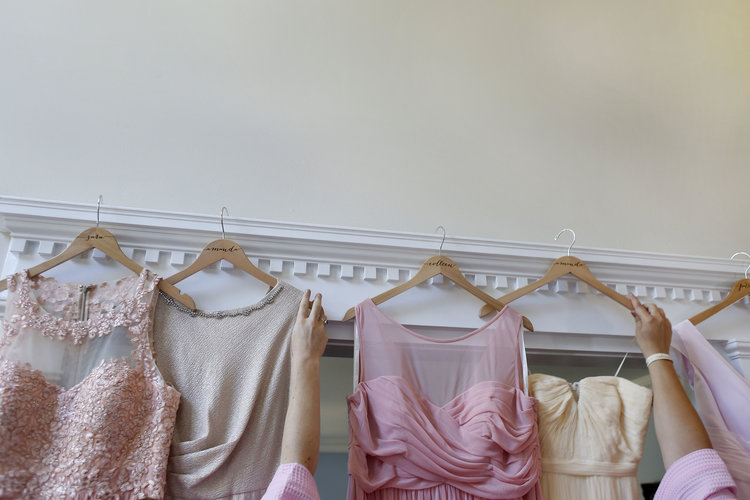Arms of women reaching for formal dresses hanging from white molding