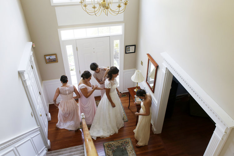 Two women fastening bride's dress downstairs in house foyer, with two other women