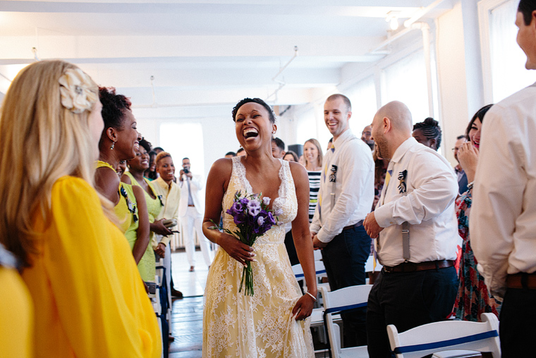Bride laughing joyfully as she walks down the aisle in a bright white room holding a bouquet of purple flowers