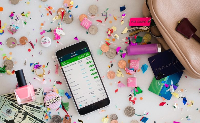 YNAB budget app on a cell phone surrounded by money and items from a woman's purse