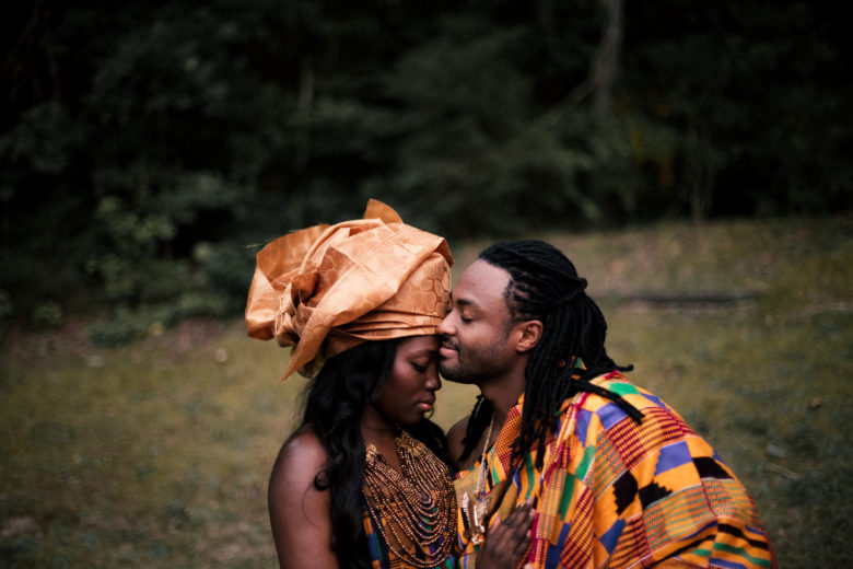 Couple wearing brightly colored clothes embracing in field