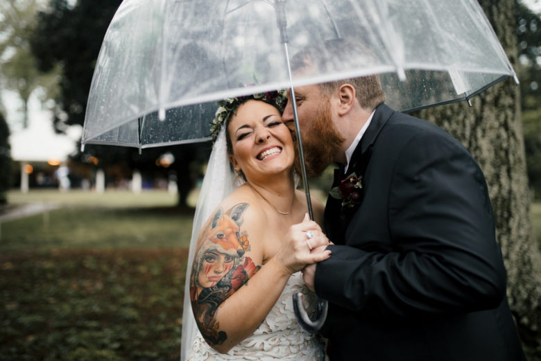 Groom kissing the cheek of smiling bride with colorful tattoo underneath clear umbrella near a tree