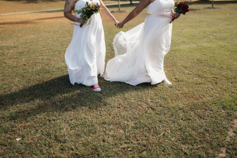 Two brides in a field wearing sneakers, holding hands and bouquets