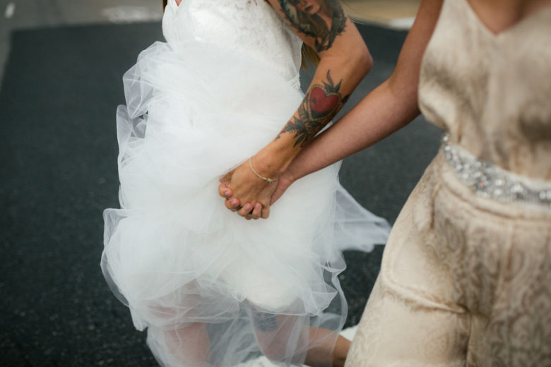 Two brides, one with tattoos on her arm, holding hands
