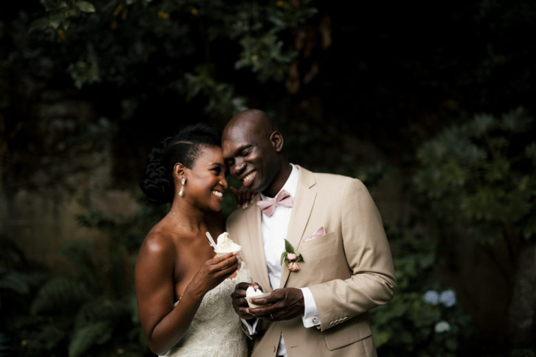 Bride and groom smiling, leaning into each other, as they hold sweet treats