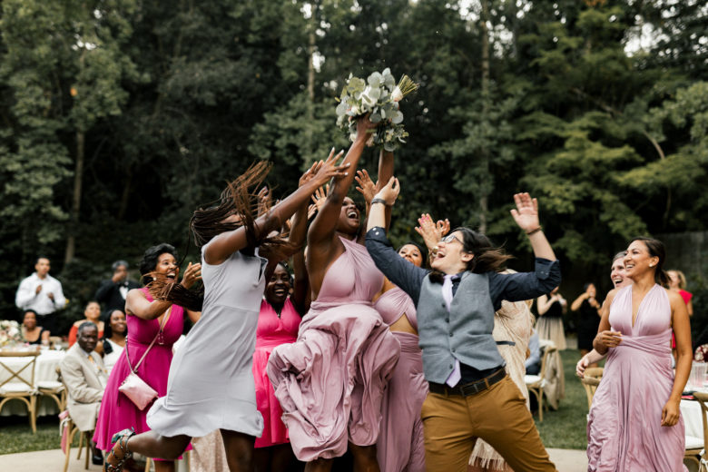 Group of people jumping for a thrown bouquet