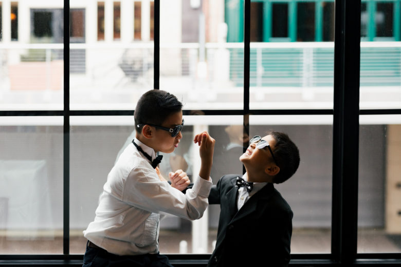 Two young boys in boy ties and glasses playing around in front of warehouse style window