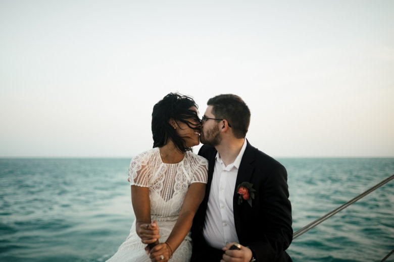 Bride and groom kissing on boat in the water