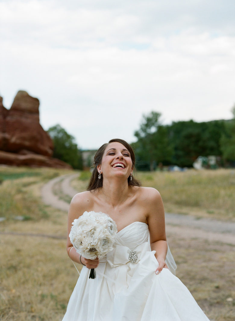 Bride in strapless dress, holding bouquet, with her head back, laughing, near dirt road
