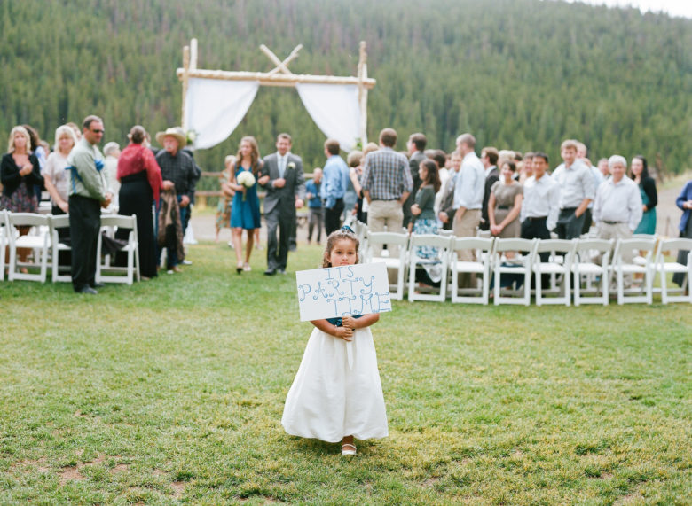 Young girl in white dress carrying a sign that reads It's Party Time down the aisle at an outdoor wedding