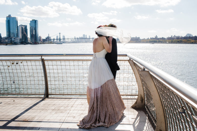 Bride and groom standing near water, overlooking skyline, with veil blowing in the wind, obscuring faces