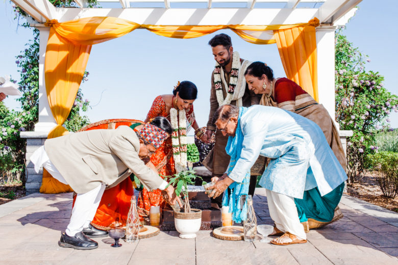 Family members planting and watering tree in small pot with bride and groom