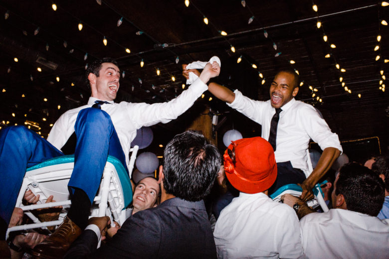 two joyful grooms being hoisted in chairs by wedding guests beneath illuminated string lights