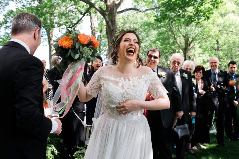 bride laughing holding a bouquet of orange flowers in front of besuited guests
