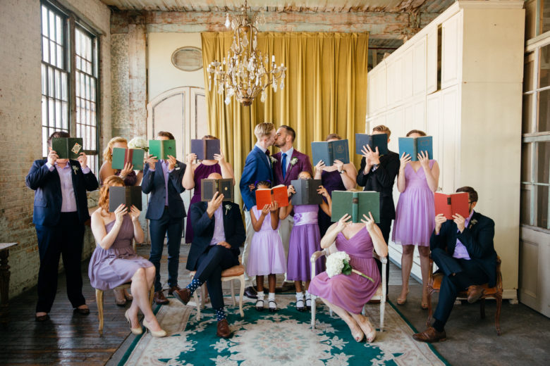 Wedding party in purple and navy holding books in front of faces as two grooms kiss under chandelier