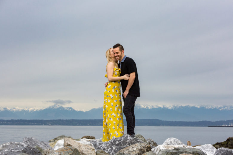 woman in yellow flower dress kissing man in black's cheek as he laughs, as they stand on rocks in front of mountains across water