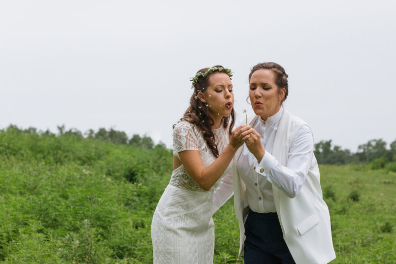 two brides in a field blowing on a dandelion