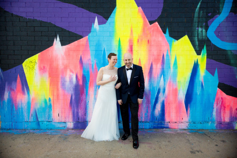 bride and groom in front of colorful graffitied brick wall