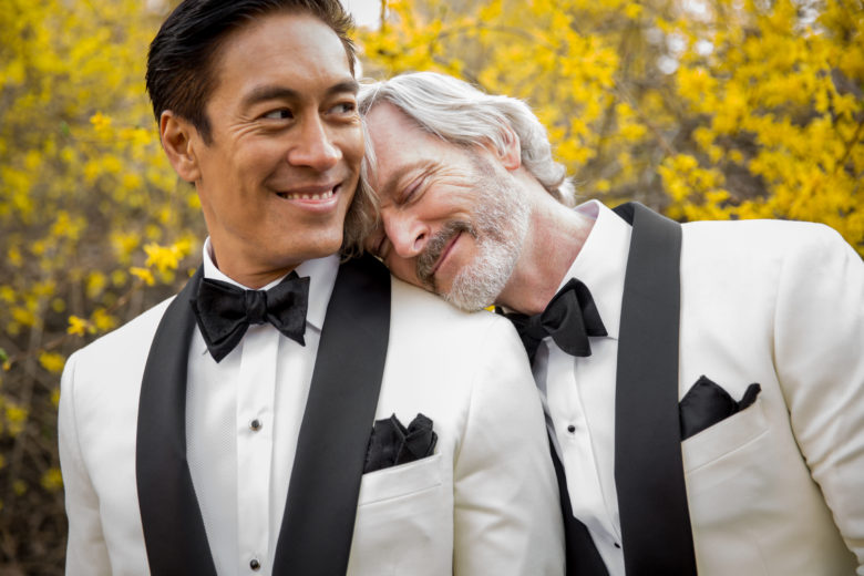 groom with his head on the shoulder of his groom, both in white and black tuxes, with yellow blossoms behind them