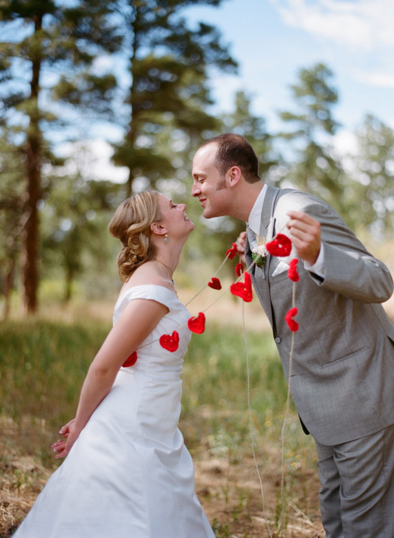 bride and groom leaning in for a kiss outside among trees, groom has string of crocheted red hearts looped around bride to draw her in.
