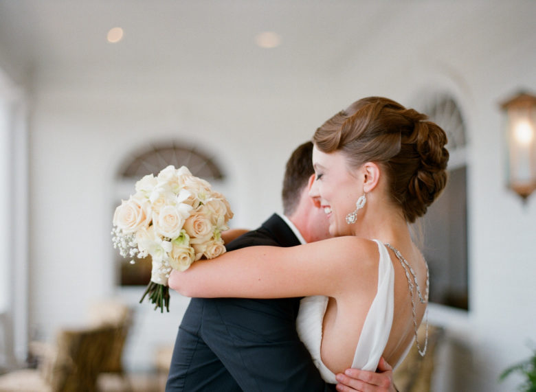 bride smiling with eyes closed embracing groom