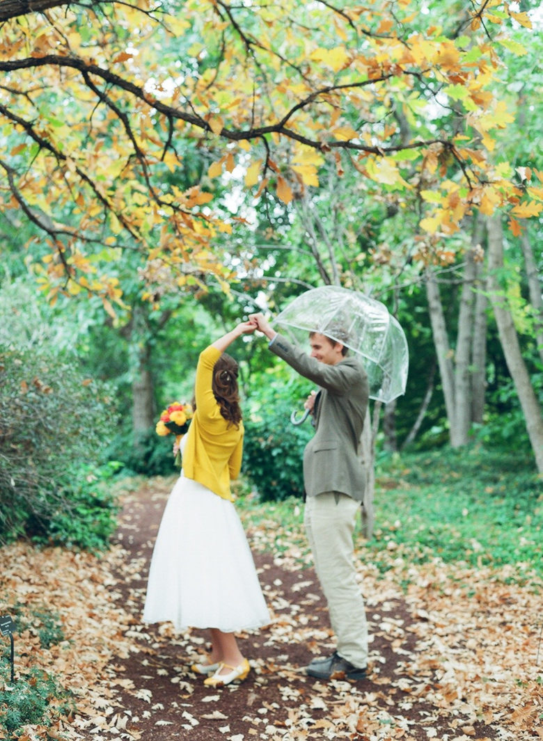 groom with clear umbrella twirling bride wearing yellow sweater under tree with yellow and orange trees in woods