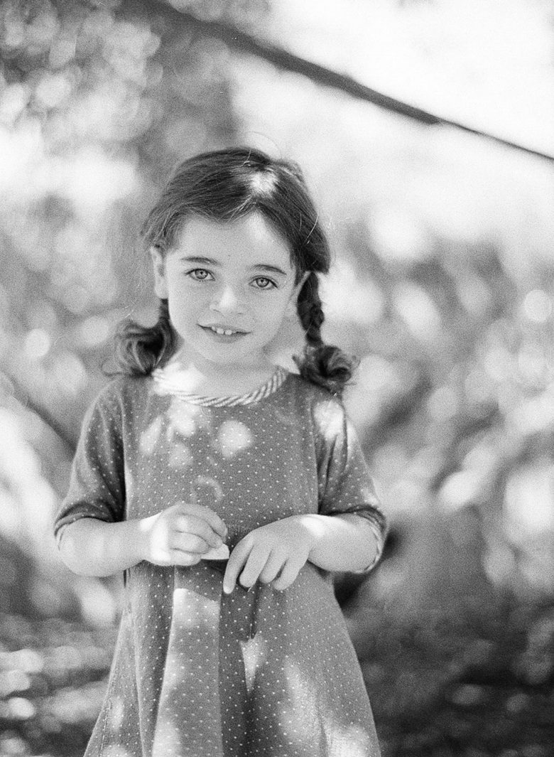 young girl with pigtail braids, smiling, looking at the camera, standing in light filtered through trees, in black and white