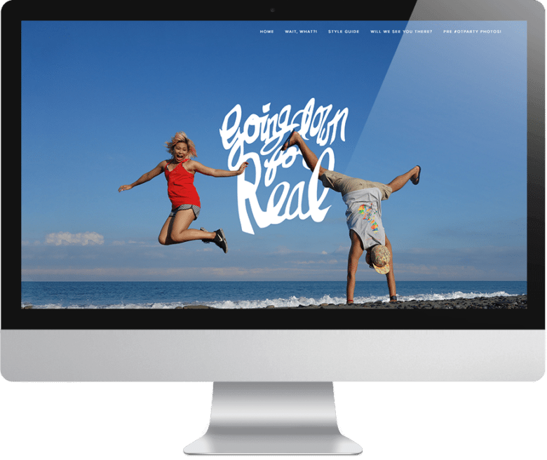 """Wedding website: Woman in red shirt jumping with joy, man in cap doing a wide-legged handstand on the beach near the water with text overlay that reads """"going down for real"""" on computer monitor"""