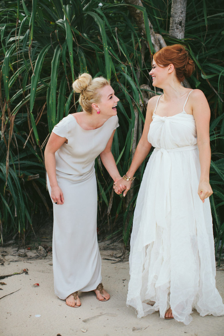 Two brides holding hands and laughing in front of tropical green plants