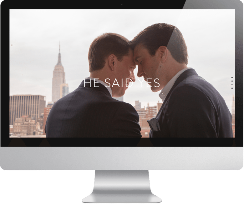 """Two happy men in suits with their foreheads together overlooking a city skyline with text overlay that reads """"he said yes"""" on a computer monitor"""