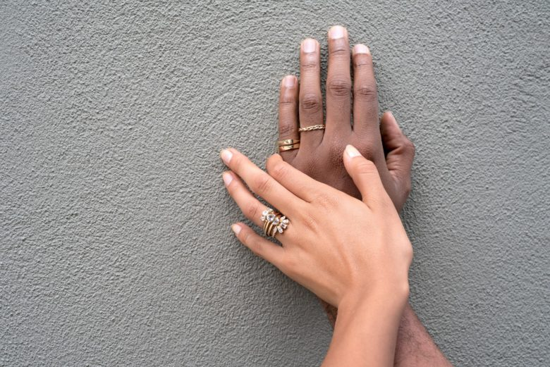 Caucasian hand with multiple diamond wedding rings on top of a black hand also wearing gold wedding rings against a dark gray wall.
