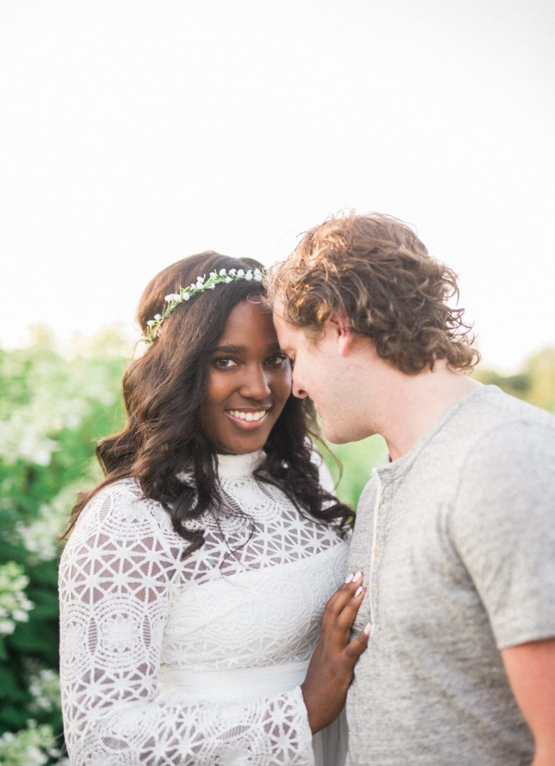Couple leaning foreheads together, bride smiling at the camera with her hand on groom's chest