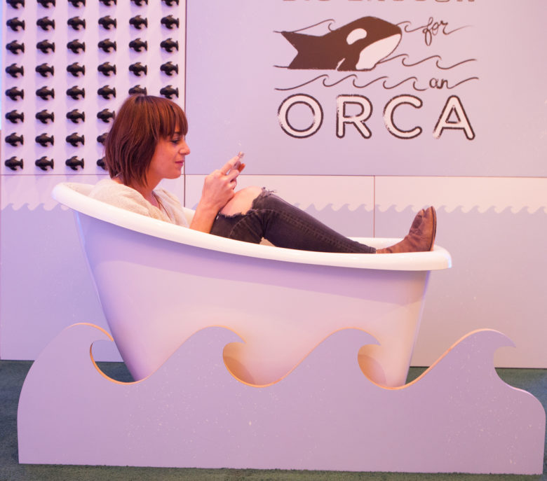 Woman sits in a bathtub, fully clothed, texting.