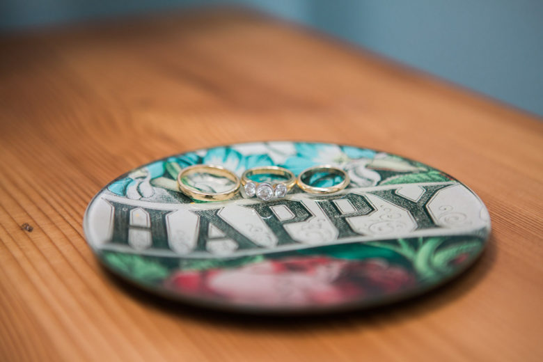 """Small round plate with the word """"happy"""" written across it with three wedding rings on it."""