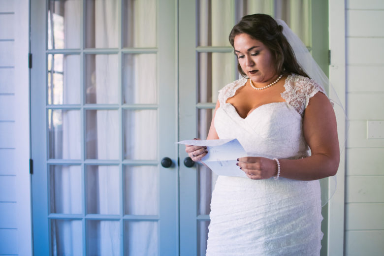 bride reads an unfolded piece of paper in front of closed french doors