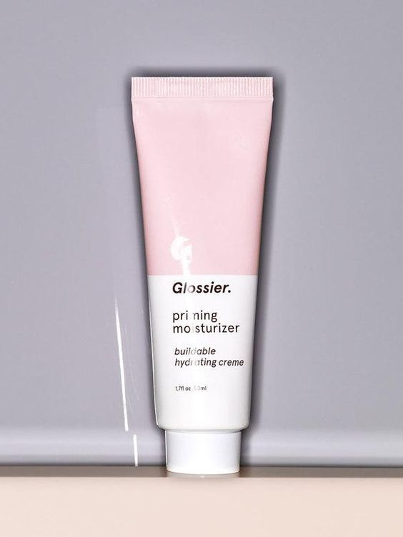 Pink and white tube of Glossier priming moisturizer on gray background