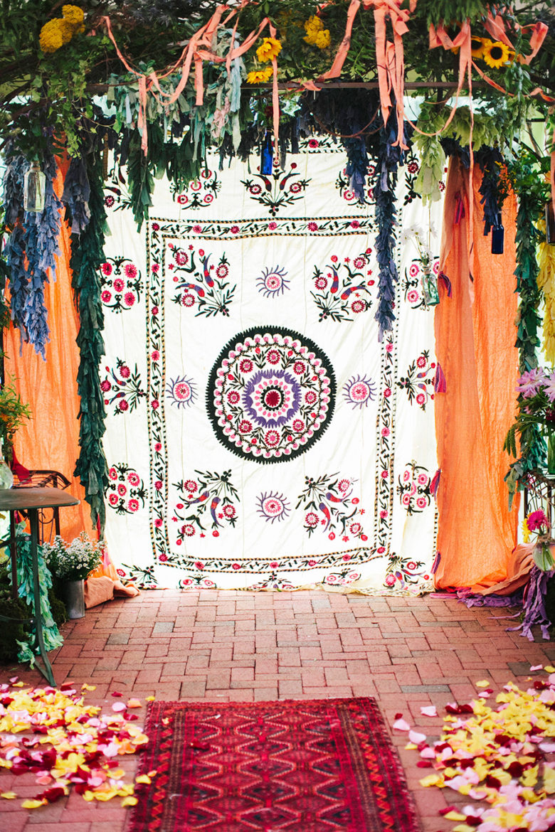 Wedding ceremony area with wall tapestry backdrop and rugs as wedding decorations