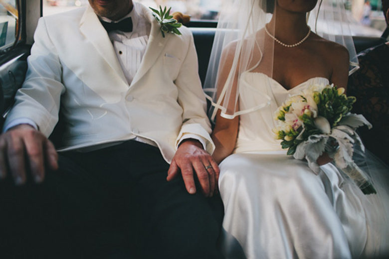 A wedding couple sit in the back seat of a car, holding hands.