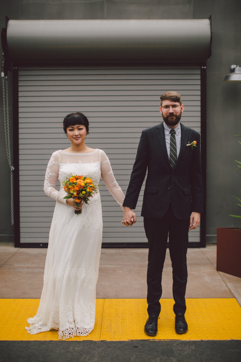 A wedding couple hold hands